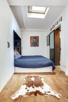 Encastré dans les rangements, la tête de lit bleu nuit apporte du caractère à la chambre