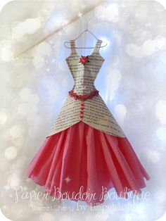 This pretty dress miniature is made from pages from a book and serviettes. The bodice detail is carefully stitched in pink cotton, and has a cherry