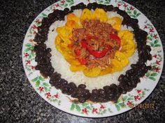 Rice, black beans, shredded meat (ropa vieja) and fried green plantains.