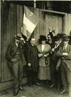"Ireland, Civil War: ""A glum group of civilians; one is holding a tricolour aloft to which is attached a small holy picture of the sacred heart; a priest and a very formidable looking woman are holding rosary beads while the man beside them is touching his hat and looking very perplexed."" UCD Digital Library, Desmond FitzGerald Photographs, Photograph by the Press Photographic Agency, London"