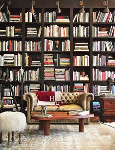 Library with floor to ceiling shelves, a leather  sofa, and a Hermès Avalon Blanket