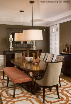 Brown dining room with an orange and white area rug, hardwood floors, dark wood furniture and an upholstered bench for extra seating. Click on the pin to get help with your next design. #bench #diningroom