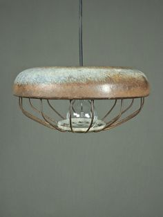 """it's all in the patina.  reusing industrial parts to great effect, the cap light is a beautifully finished metal work of art + craft. rusted in all the right places, this light is perfectly scaled for a counter, to dwell over a kitchen sink or lit above a bathroom vanity.  please note - due to their repurposed nature markings + coloring may vary  dimensions: 13""""dia. x 6""""h  cord length: 5""""l"""