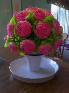 This is made of cupcakes attached to a styrafoam ball, with toothpicks. The green is a plastic tablecloth cut into small pieces with pinking sheers, then tacked in between the cupcakes. The ball is placed on an upside down cake stand. I'd also use a flower pot!
