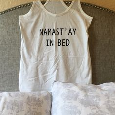Namast'ay In Bed Tank White tank. Black writing. Racerback. Back is plain. 100% cotton. Made in Bangladesh. No trades. Price is firm. BUNDLE TO SAVE! Iconic Legend Tops Tank Tops