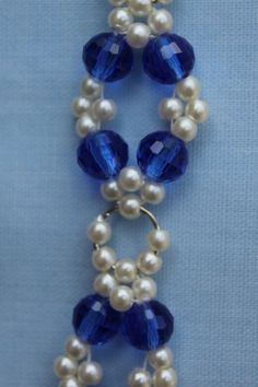 "This bracelet has blue transparent faceted beads and round pearl beads. Each blue and pearl pattern are joined with a silver coloured jump ring. It has an adjustable length.   Shortest length: 19cm (7½"").  Longest length: 26cm (10.25"").  Materials used: Glass, acrylic and silver coloured metal."