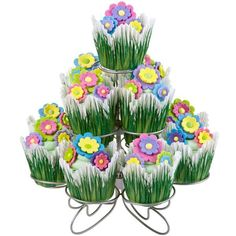 Flora Cupcakes Display - Springtime is the theme of this pretty cupcake display. Easy to make, the cupcakes are baked in grass baking cups, iced in buttercream icing and topped with Multi Flower Icing Decorations. Display them on the Cupcakes-N-More Stand at your Easter or spring celebration!