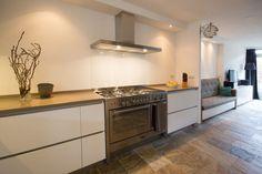 Greeploze, hoogglans witte keuken met aansluitend een zitbank en tv-meubel in dezelfde stijl