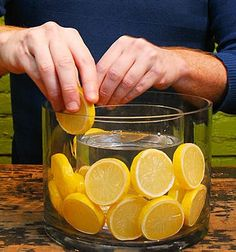 Lemon Slices as Centerpiece..also like the idea of a smaller container inside to hold the flowers etc.