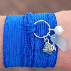 One of our newest creations, a lovely blue silk wrap bracelet with sea glass, freshwater pearl and tropical fish charm. One size fits all. $42 from www.seaglassjewelrybyjane.com