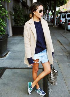 Sincerely Jules wears the perfect spring outfit in a navy sweater, cut-offs, and classic camel blazer