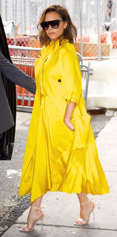 Victoria Beckham broke out of her color comfort zone and lit up the streets of New York City in a cheery satiny yellow wrap dress that she styled with a matching yellow topper, black shades, and nude sandals.