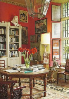 floor to ceiling windows, red walls, oriental rug, eclectic and diverse furniture and pictures.  What a library!