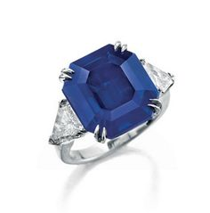 A Fine Sapphire and Diamond Ring Set with an octagonal-cut sapphire, weighing approximately 12.06 carats, flanked on either side by a triangular-cut diamond, mounted in platinum With report 14070286 dated 6 August 2014 from the Gübelin Gem Lab stating that gemmological testing revealed characteristics consistent with those of sapphires originating from Kashmir. No indications of heating; accompanied by a supplemental appendix attesting to the rarity of the sapphire
