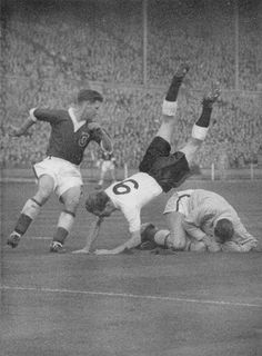 14th November 1956. Wales goalkeeper Jack Kelsey diving at the feet of England centre forward Tom Finney, at Wembley.