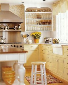 I love this creamy yellow kitchen. I love wallpaper in a kitchen, and in such a lovely pattern...