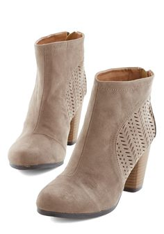 Cutouts adorning taupe-hued booties