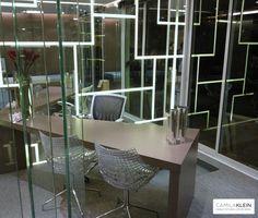Escritório com painel de chassi de madeira, espelhos e iluminação de LED, inovador e singular. A iluminação de LED desenha geometrias na parede e traz um clima ousado e futurista, que é quebrado com a bancada de marcenaria e o piso texturizado, trazendo aconchego para o ambiente de trabalho.  #arquitetura #camilakleinarquiteta #interiordesign #office #escritorio #work #led #iluminacao