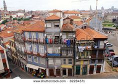 Typical old buildings in Porto(Portugal). Narrow streets, red roofs,multicolored  tile decor on the walls, small balconies with washing and portuguese flag. It's very special town.
