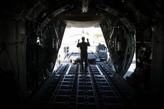 A loadmaster with the 36th Airlift Squadron marshalls cargo on to a C-130 Hercules April 23, 2014 at Yokota Air Base, Japan. The sortie took off in support of Max Thunder, a bilateral aerial training exercise that trains U.S. and Republic of Korea Air Force pilots to work closer together against a hostile force. (U.S. Air Force photo by Staff Sgt. Chad C. Strohmeyer/Released)