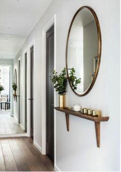 Idea para crear un recibidor con espejo redondo y repisa de madera