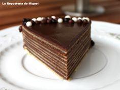 Baumkuchen.Foto frontal de la porción de pastel, presentado en un plato blanco de porcelana  con ramillete de flores. El pastel  esta decorado alrededo...
