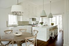 Barbara Waltman Design: Beautiful white kitchen and dining area with green tile backsplash, mint green hanging lamps, drum pendant, calcutta marble, pedestal kitchen table, light wood French cafe chairs,  backless seagrass counter stools,