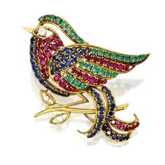 18 KARAT GOLD, COLORED STONE AND DIAMOND BIRD BROOCH Designed as a bird perched on a gold branch, set with round sapphires, emeralds and rubies, the eye and leaves set with small round diamonds.