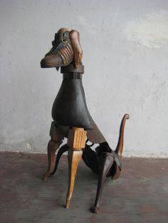 Cet oeuvre est un chien en matériaux recyclés. Selon moi la technique utilisée est la sculpture. Il n'y a pas beaucoup de couleurs, par contre on peut voir que l'artiste a utilisé un soulier pour faire la tête et des pattes de chaises pour faire les pattes et la queue du chien. En observant cet oeuvre, j'ai ressenti de l'étonnement et de la surprise car au début je n'avais pas réalisé que ce chien était fait avec des matériaux recyclés.