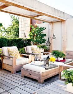 Contemporary-rustic furniture, accents serving as pops of color, wood, and plenty of sprawling greenery make this rooftop a place of refuge.