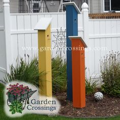 Fun garden bird houses made out of 1x6 boards and painted in fun colors. Super easy garden craft that could be done together as a family! Love the bright colors in the bright colors in the garden.  www.gardencrossings.com