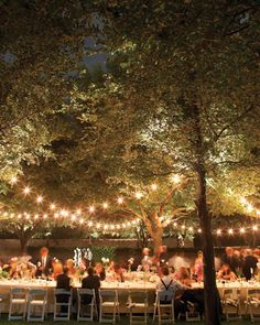 Two long rectangular tables are arranged side-by-side in the garden under strings of twinkling lights to encourage casual conversation during the alfresco celebration.