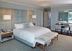 une tête de lit grise et des murs en bleu pâle dans la chambre à coucher