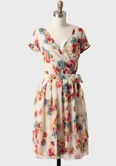 Blended Blossoms Dress: A gorgeous watercolor floral print design adorns this delicate cream-hued dress. Perfected with a flattering surplice neckline and buttons at the waist, this elegant wrap dress features a waist-defining sash. Fully lined. By DownEast Basics.