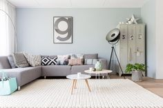 Love the gray sectional sofa; black-and-white print pillows with touches of mint and pink; two small round tables; plant in bag; standing lamp