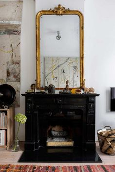 ornate gold mirror over black fireplace / sfgirlbybay