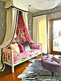 source: Kriste Michelini Interiors Fun girl's bedroom with Osborne & Little Minaret Wallpaper, West Elm Window Daybed, pink bolster pillows, ivory linen canopy with black ribbon trim, zebra cowhide rug, round purple tufted ottoman, ivory curtains with black ribbon trim and Z Gallerie Jupiter Chandelier. decorpad.com