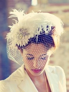 It has a handmade real swarovski crystal flower with an iridescent amber center placed on the edge of a silk covered hand blocked buckram hat. The plumpest ostrich plumes in are set across it as well as a spray of smooth ivory white feathers.The veil is covered in tiny crystals as well.