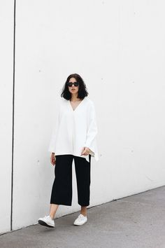 Elisa from the Fashion- and Lifestyleblog www.schwarzersamt.com is wearing a new black white outfit with goliath sportswear sneaker, COS Sale Tunic, H&M Trend Culotte, Sunbuddies Eyewear and Weekday and & Other Stories Jewellery. It's a minimalistic and clean black and white outfit.