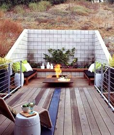 A concrete block retaining wall is a good solution for building a modern deck into a hillside. I love the Corten steel fire pit, and how they painted just .