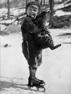 1940: A young boy on skates clutches a large tabby cat. Photo courtesy of Getty Images.