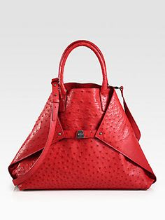 "Akris Ai Medium Ostrich Bag in Red.    Ostrich foldover trapezoid silhouette cinched by a center turn-lock buckle closure.  Double top handles, 5½"" drop  Detachable shoulder strap, 24"" drop  Top snap closure and versatile turn-lock buckle closure, can be tucked into bag for a tote silhouette  One inside zip pocket  Two inside open pockets  Leather lining  15""W X 12""H X 4½""D  Imported"