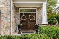 Welcoming front door with dark stained hardwood, floral wreaths, potted plants and a welcome mat. Listed in Vienna Virginia by The Casey Samson Team is a Wall Street Journal Top Team in Northern Virginia.