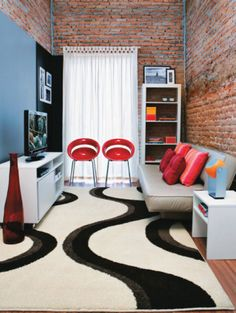 O design desta sala apresenta móveis pouco volumosos e aposta em cores neutras que funcionam com a parede de tojolinho. O sofá-cama amplia a função do espaço, que também pode ser usado como quarto de hóspedes.