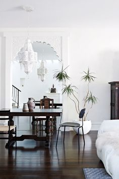 Dining room with white washed walls, carved white mirror Moroccan lamp with matching pendant light, dark wood floors and Middle Eastern inspired table and chair