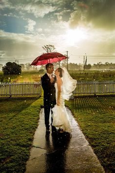 Sunshower, beautiful wedding and a quaint red umbrella - what's not to love?! photo by Heath Wade Photography