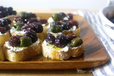Roasted Grape and Olive Crostini Recipe Appetizers with olive oil, grapes, olives, rosemary, sea salt flakes, baguette, ricotta -- this might be worth playing with???