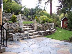 aménagement jardin en pente avec murs de soutènement et marches en pierre
