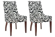 Add a wild punch to any space with the zebra-print fabric of this duo of dining chairs