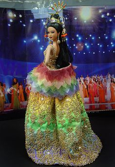 """OOAK Barbie NiniMomo's Miss Bali 2010 ~ From the famed paradise Indonesian island of Bali comes 1 of our most decadent & opulent showpiece Delegates to date, 5 mo. in the making. She's resplendent in a rainbow themed evening gown w/ a sheer, nude mesh top that has been gorgeously hand-beaded at bodice as an illusion """"bra"""" style intricately hand-sewn gold beadwork. Draping from bra top down through stomach are hand-beaded tiers of more beadwork in gold w/ colorful accents of tiny minuscule…"""